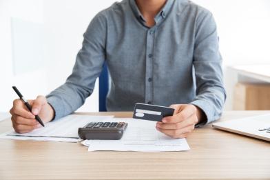 Man writing credit card number at desk